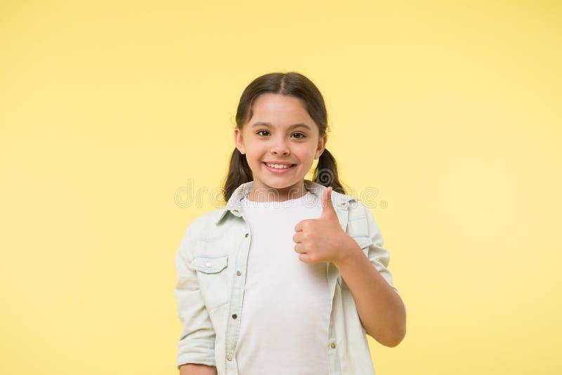 Gute Qualität Kindermädchen-Showdaumen herauf Geste empfiehlt gelben Hintergrund Kind empfehlen in hohem Grade sich mit dem Daume lizenzfreie stockfotos