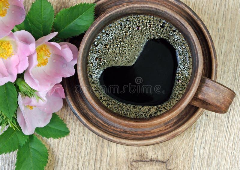Guten Morgen ein Tasse Kaffee und ein rotes wildes stiegen auf einen Holztisch Herz ist ein Symbol der Liebe stockfotografie