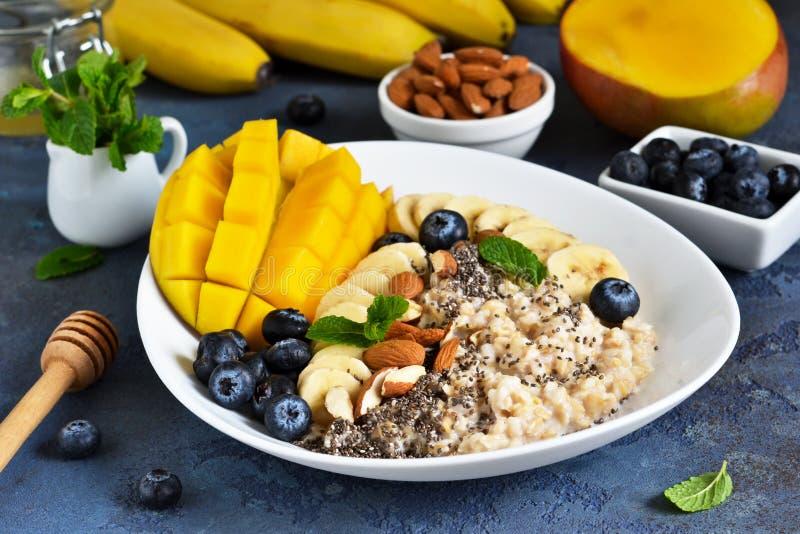 Guten Morgen! Frühstück mit Hafermehl, Banane, Mango, Blaubeeren und chia Samen auf einem konkreten Hintergrund stockbilder
