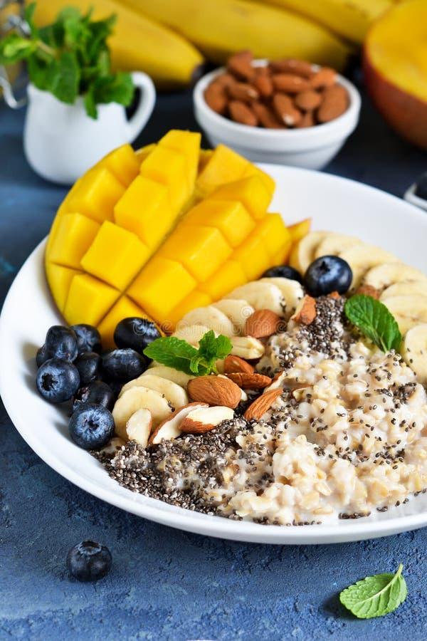 Guten Morgen! Frühstück mit Hafermehl, Banane, Mango, Blaubeeren und chia Samen auf einem konkreten Hintergrund stockbild