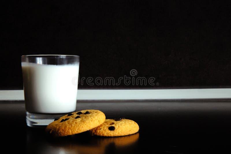 Guten Morgen Frühstücks-Plätzchen und ein Glas Milch joghurt Schwarzer Hintergrund Minimales Schwarzweiss lizenzfreies stockfoto