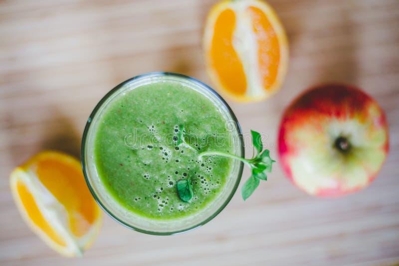 Guten Morgen: Frischer grüner Smoothie und Früchte auf hölzernem Hintergrund, gesundes Frühstück lizenzfreie stockfotos
