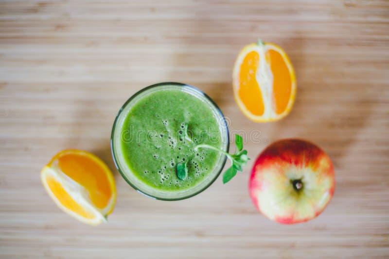 Guten Morgen: Frischer grüner Smoothie und Früchte auf hölzernem Hintergrund, gesundes Frühstück lizenzfreies stockbild