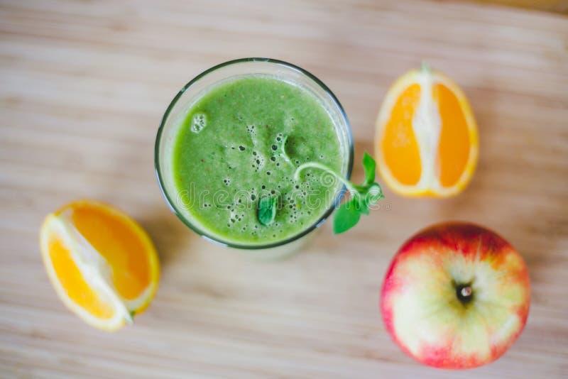 Guten Morgen: Frischer grüner Smoothie und Früchte auf hölzernem Hintergrund, gesundes Frühstück lizenzfreies stockfoto