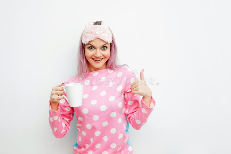 Guten Morgen Lächelnde junge Frau zeigt sich Daumen Mädchen in den rosa Pyjamas und in der Schlafmaske lizenzfreie stockbilder
