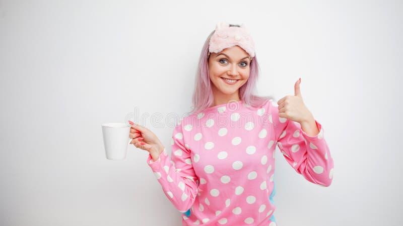 Guten Morgen Lächelnde junge Frau zeigt sich Daumen Mädchen in den rosa Pyjamas und in der Schlafmaske stockbild