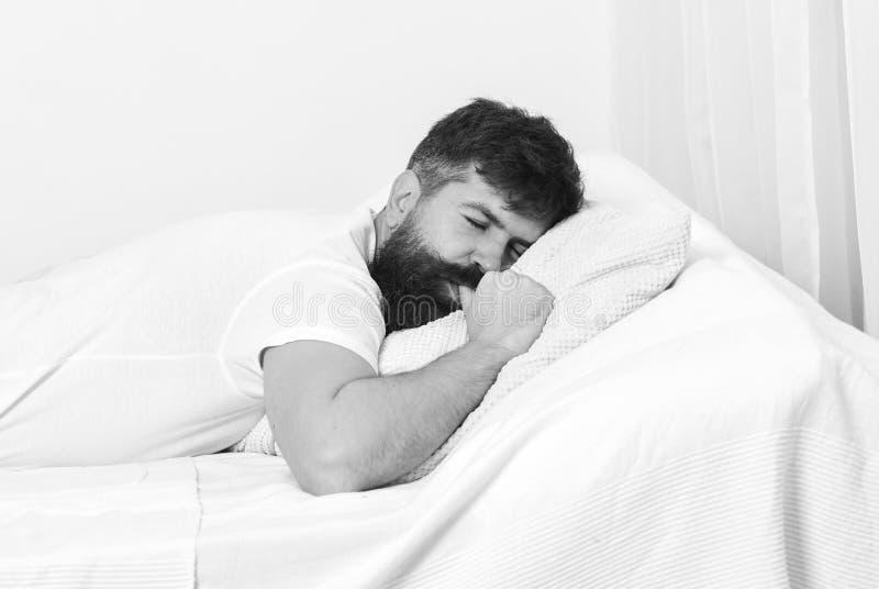 Guten Morgen Mann im Hemd, das auf Bett, weiße Wand auf Hintergrund legt Haar- und Siestakonzept Kerl, der Daumen während saugt stockbild