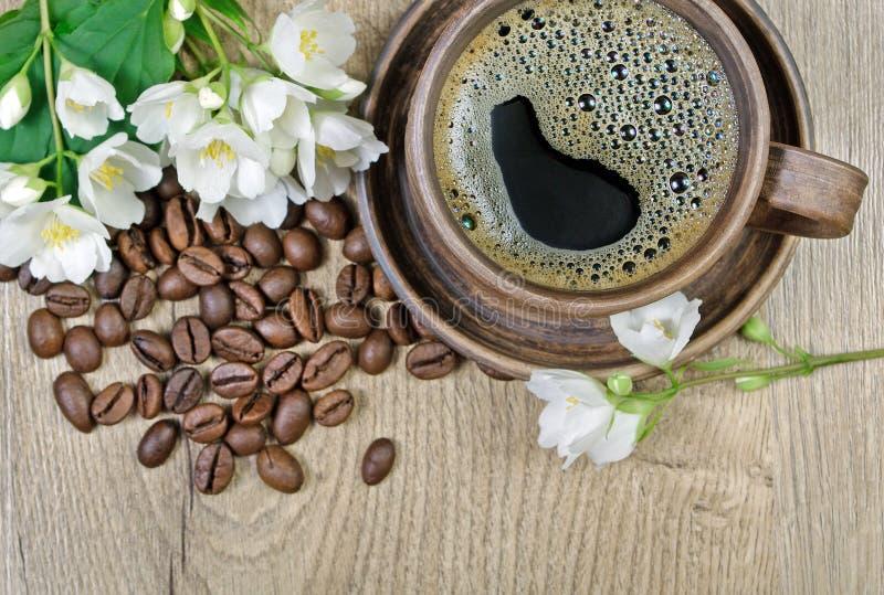 Guten Morgen Morgenkaffee- und -jasminblumen auf einem Holztisch lizenzfreies stockfoto