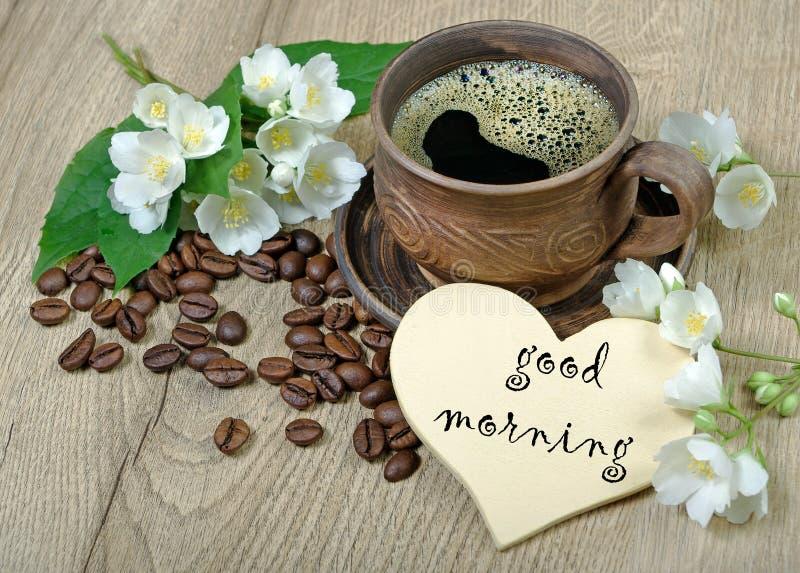 Guten Morgen Morgenkaffee- und -jasminblumen auf einem Holztisch lizenzfreies stockbild
