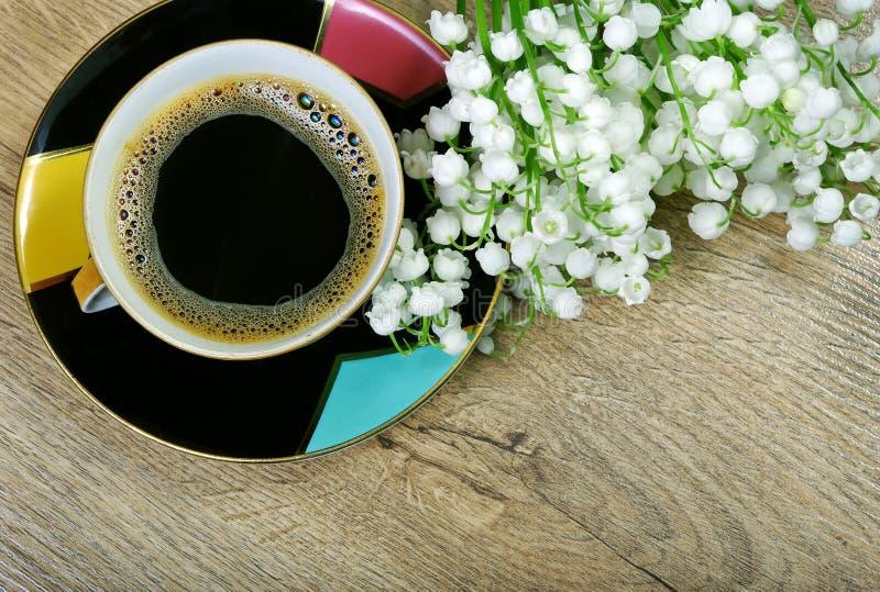 Guten Morgen Morgenkaffee und -Maiglöckchen blühen auf einem Holztisch lizenzfreies stockfoto