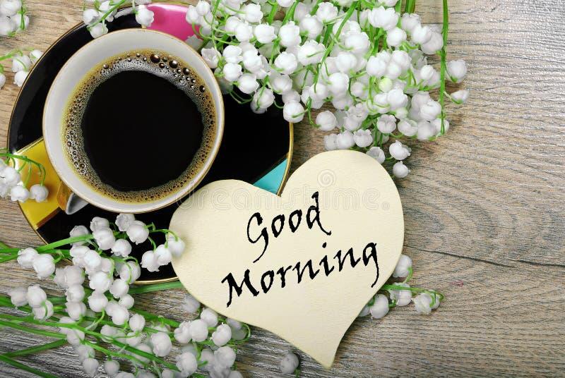 Guten Morgen Morgenkaffee und -Maiglöckchen blühen auf einem Holztisch lizenzfreie stockbilder