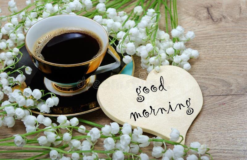 Guten Morgen Morgenkaffee und -Maiglöckchen blühen auf einem Holztisch stockbild
