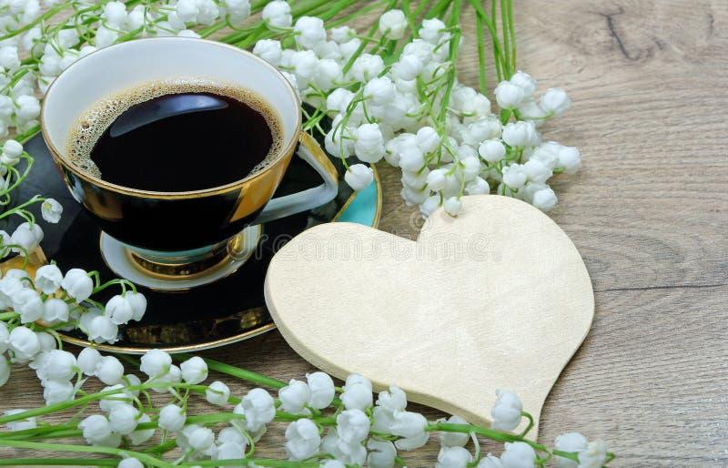 Guten Morgen Morgenkaffee und -Maiglöckchen blühen auf einem Holztisch lizenzfreie stockfotos