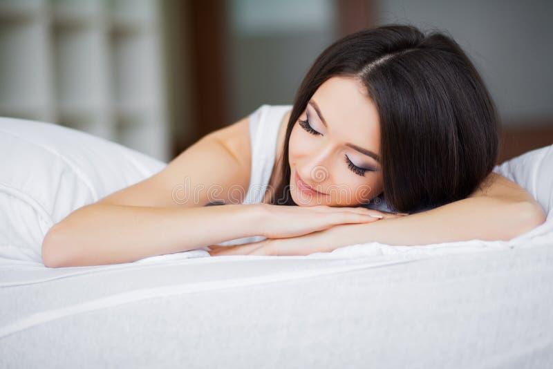 Guten Morgen Porträt von lächeln recht junge Brunettefrau, die im weißen Bett sich entspannt stockfoto