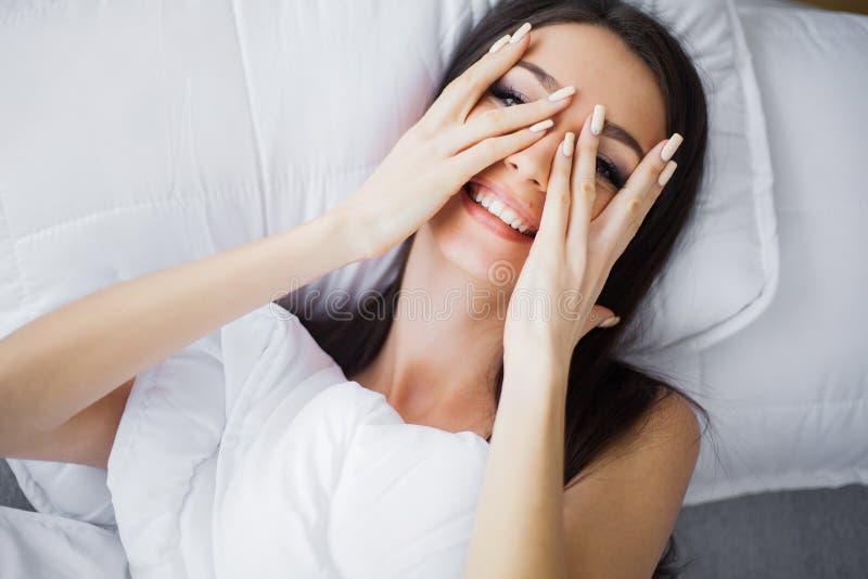 Guten Morgen Porträt von lächeln recht junge Brunettefrau, die im weißen Bett sich entspannt lizenzfreie stockfotos