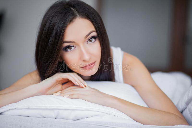 Guten Morgen Porträt von lächeln recht junge Brunettefrau, die im weißen Bett sich entspannt lizenzfreie stockfotografie