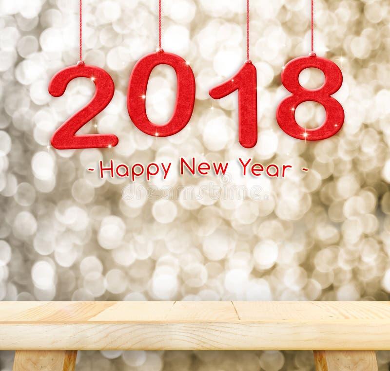 2018 guten Rutsch ins Neue Jahr, das über einfacher hölzerner Tischplatte mit Unschärfe hängt stockbilder