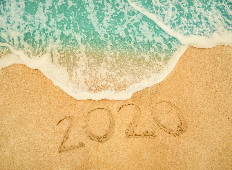 Guten Rutsch ins Neue Jahr 2020 geschrieben auf Küstensand am Sonnenaufgangkonzept stockfoto