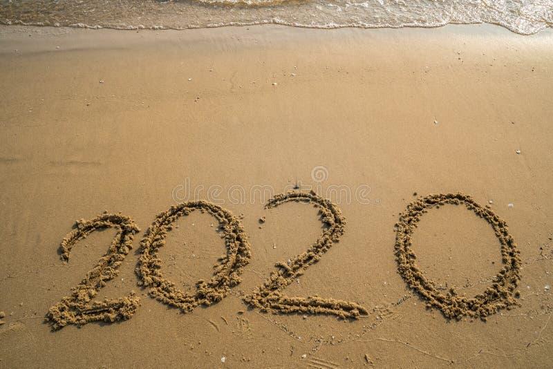 Guten Rutsch ins Neue Jahr-Konzept 2020, Beschriftung mit 2020 Zahlen auf dem Seestrand, Welle und goldenes Licht des Sonnenunter lizenzfreie stockfotografie