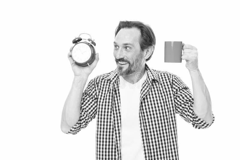 Gutenmorgen holt einen guten Tag Reifer Mannholdingwecker und -schale B?rtiger reifer Mann mit analoger Uhr und Becher lizenzfreie stockfotos