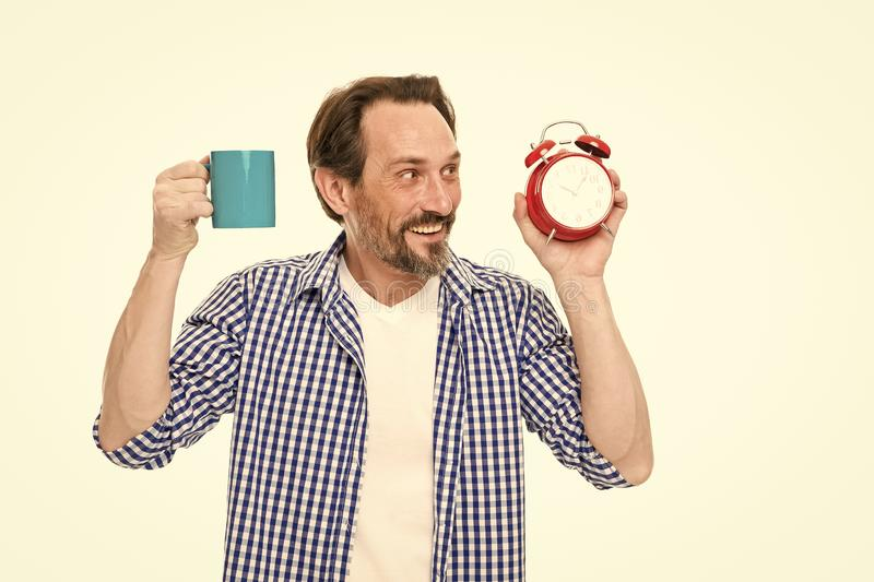Gutenmorgen holt einen guten Tag Reifer Mannholdingwecker und -schale B?rtiger reifer Mann mit analoger Uhr und Becher lizenzfreie stockbilder
