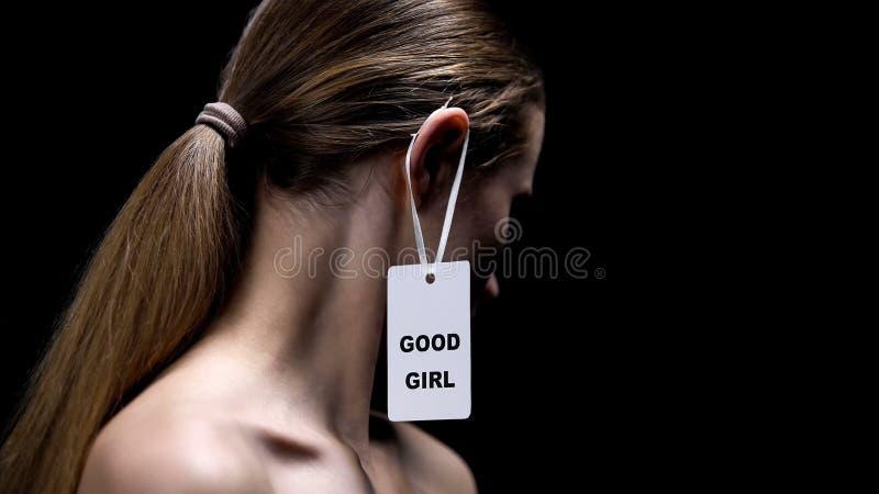 Guter Mädchenaufkleber auf weiblichem Ohr, imponierende männliche Meinung, schwarzer Hintergrund, Nahaufnahme lizenzfreie stockfotografie