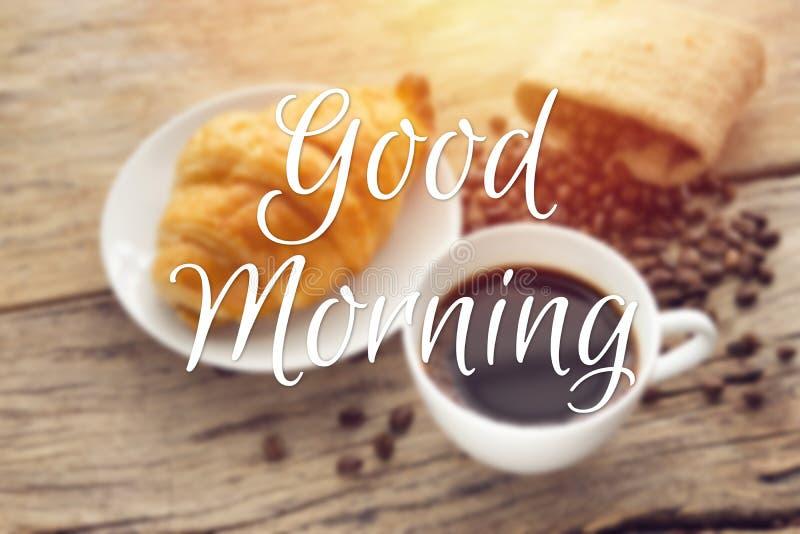 Guter Morgen des Textes mit undeutlichem des kontinentalen Frühstücks mit frischem Hörnchen und heißem Kaffee auf Holztisch, Deko stockfotos