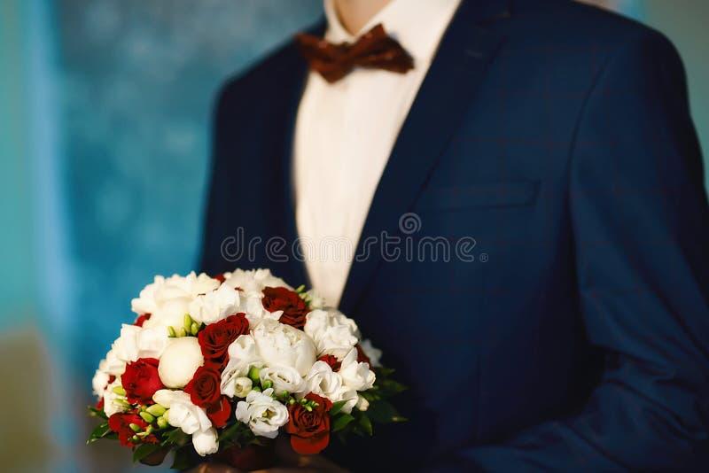 Gutes Morgenkochen, schöne Braut, gekleidet und für eine Hochzeit, in einer Klage mit einem Blumenstrauß von Blumen vorbereitend stockfoto