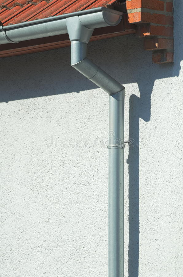 Gutter on a House. Grey Metal Gutter on a White House Vertical royalty free stock images