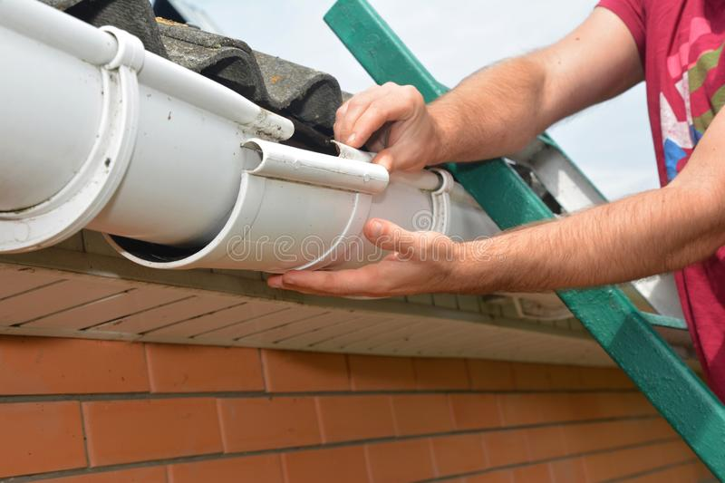 Gutter pipeline installation. Roofer contractor installing and repair rain gutter. Guttering repair. With contractor hands stock photography