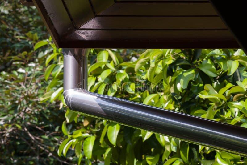 Gutter. Silver metal rain gutter system with wooden decking stock photo