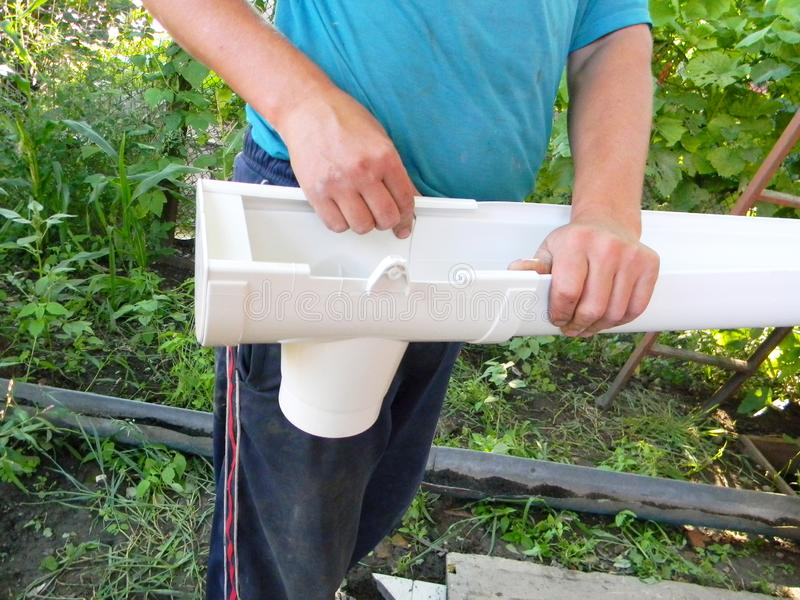 Guttering?? 安装雨天沟水落管排水管的承包商 库存照片