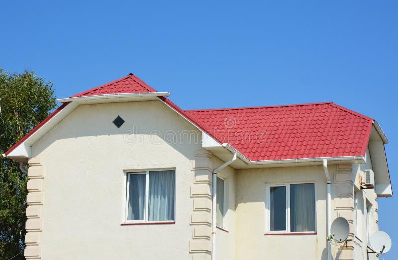 Guttering met het rode dak van het metaalhuis Dak guttering pijpleiding sys royalty-vrije stock fotografie
