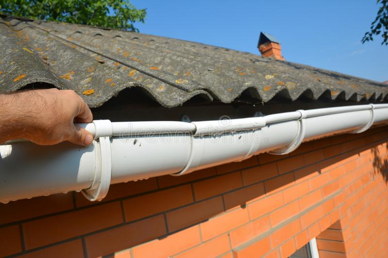 Guttering repair with contractor hands. Asbestos roof gutter repair stock photography