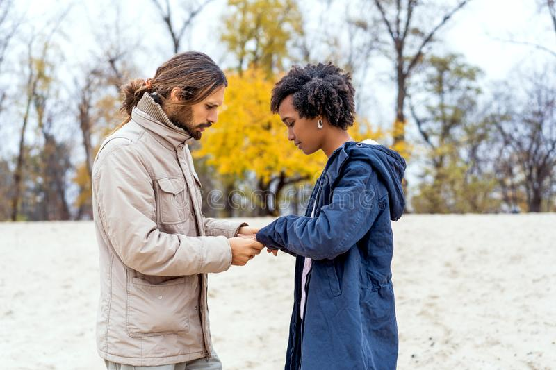 Guy with an african american girl in love in autumn park makes her an offer to get married royalty free stock photos