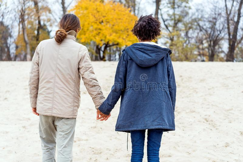 Guy with an african american girl in love in autumn park walk at sunset royalty free stock photo
