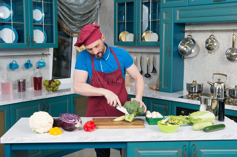 A Guy in apron preparing broccoli. chef cutting broccoli at home kitchen. A man cuts up fresh broccoli on a cutting board. royalty free stock photography