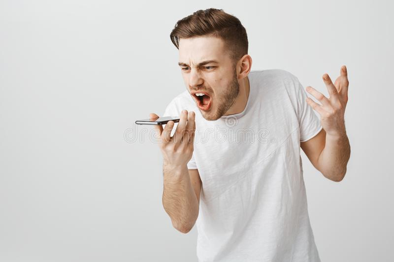 Guy arguing via phone call being fed up shouting at smartphone speaker bending towards gadget yelling at screen. Frowning from outrage ending up relationship stock photos