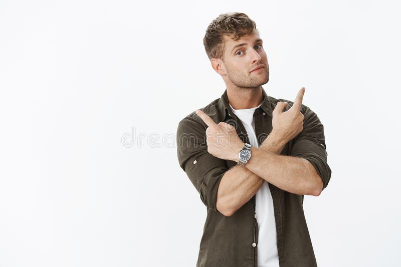 Guy asking opinion or advice as making decision being hesitant pointing sideways with crossed arms looking questioned. And curious at camera, standing against stock image