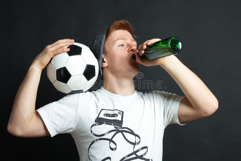 The guy with ball drinks beer stock image