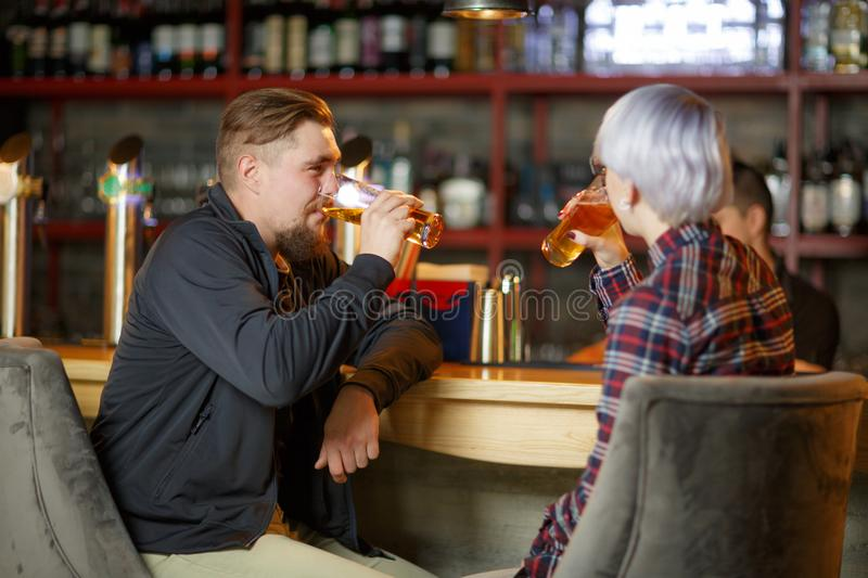 A guy with a beard and a girl with short blond hair, sitting in a bar and drinking beer. Indoors stock image