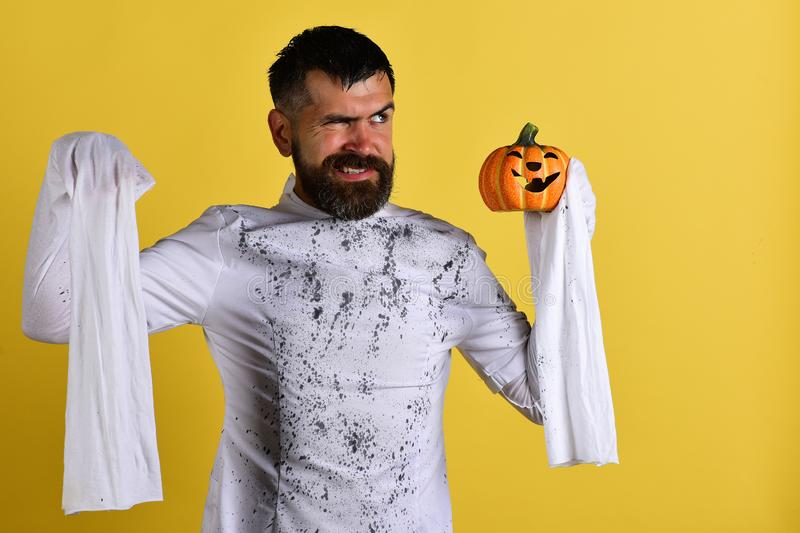 Guy with beard holds orange pumpkin with smile royalty free stock photos