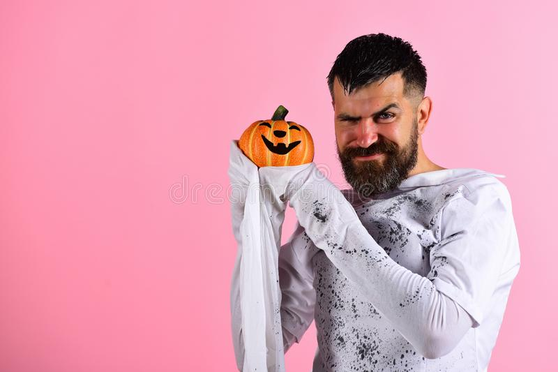 Guy with beard holds smiling jack o lantern. Halloween character royalty free stock images