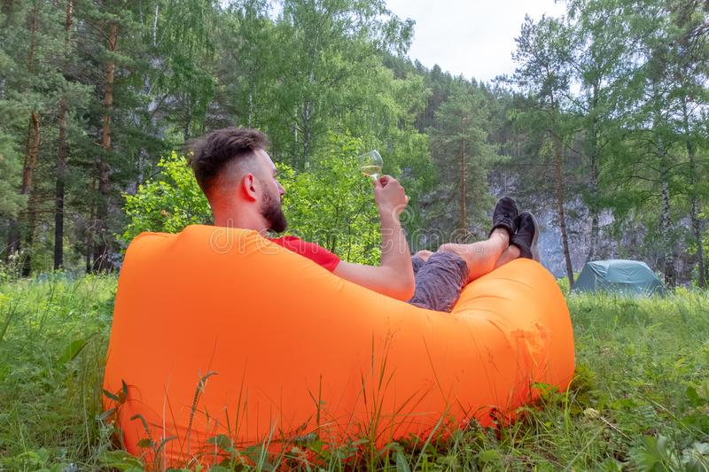 The guy with the beard in the red T-shirt lies on the orange inflatable Lamzatz sofa and looks at the glass with a white drink. royalty free stock images