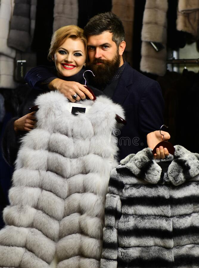 Guy with beard and woman buy furry coat. stock photography