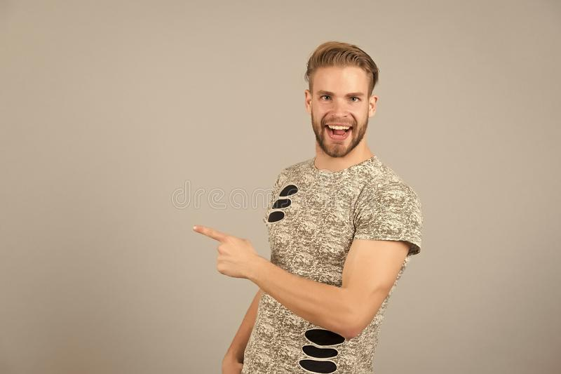 Guy bearded attractive pointing index finger to side. Advice concept. Man cheerful happy face looks successfully, grey. Background. Man with beard unshaven guy royalty free stock images