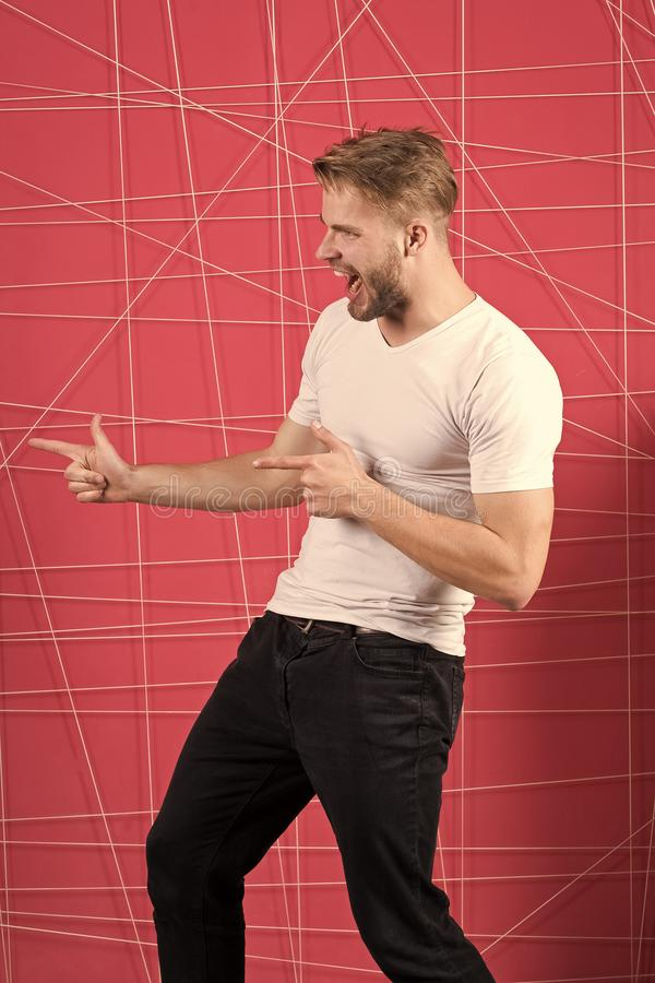 Guy bearded attractive pointing index fingers to side. Man cheerful happy face looks successfully, pink background. Success and luck concept. Man with beard royalty free stock image