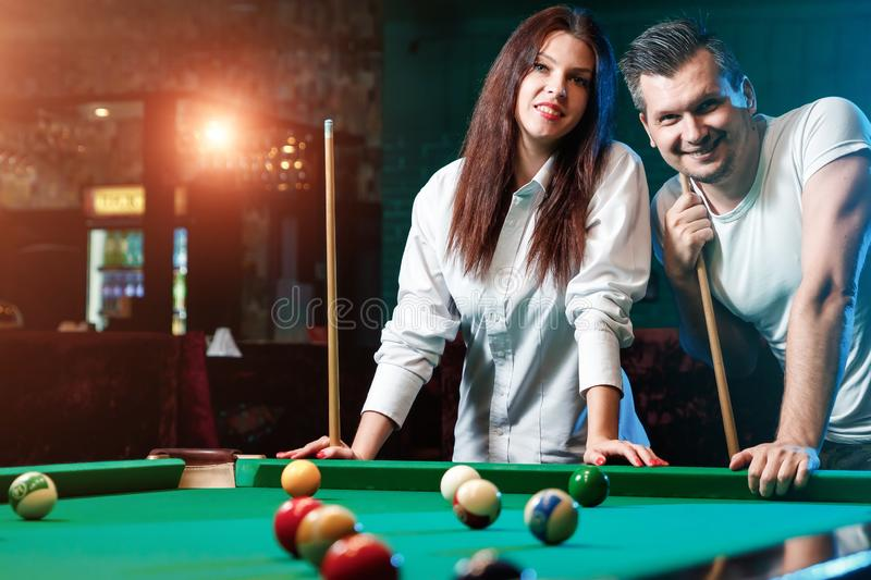 A guy and a beautiful girl are playing billiards, a guy is teaching a girl to play billiards. Dark background. Pleasant pastime, royalty free stock images