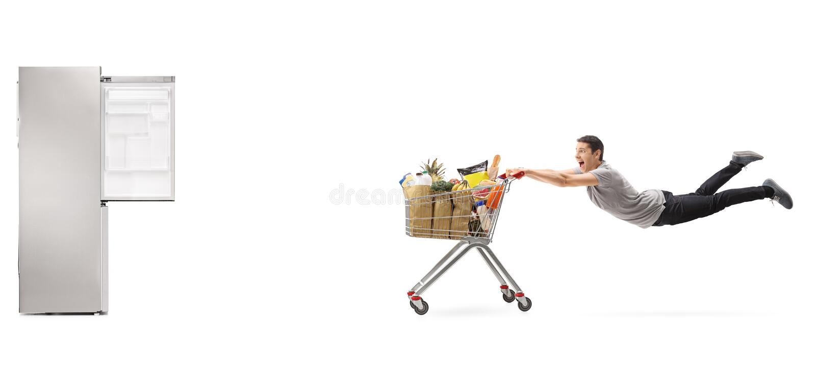 Guy being pulled by shopping cart towards an empty fridge. Guy being pulled by a shopping cart full of groceries towards an empty fridge isolated on white stock photo