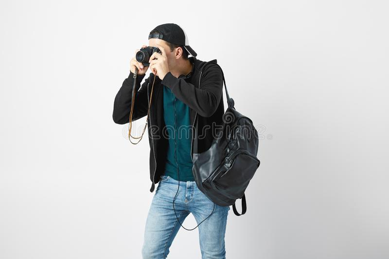 Guy with a black backpack on his shoulder dressed in a dark t-shirt, jeans, sweatshirt and a cap makes a photos in the royalty free stock photo